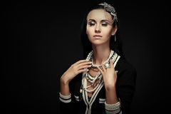 Glamorous woman with lots of jewelry on a black background Stock Photos