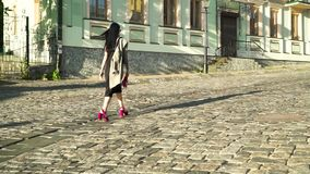 Glamorous woman with pink bag and in trendy shoes walking at stone road in city. Elegance stylish woman in black dress and grey coat is walking at the urban stock video footage