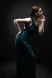 Glamorous woman posing. Glamorous woman in a blue sparkly dress posing. Dramatic lighting stock images