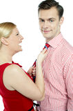 Glamorous woman pulling man by his tie Stock Images