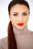 Glamorous woman in red lipstick. Glamorous elegant woman in red lipstick wearing a stylish polo neck top, head and shoulders frontal portrait isolated on white Royalty Free Stock Images