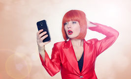 Glamorous woman in red making selfie on smartphone Stock Photo