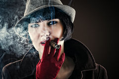 Glamorous woman in retro style with cigar. Beautiful glamorous woman in retro style with cigar Royalty Free Stock Photo