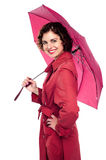 Glamorous woman standing under pink umbrella Stock Photos