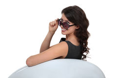 Glamorous woman in sunglasses. Glamorous woman wearing sunglasses and sitting in a designer chair Stock Photos