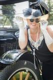 Glamorous Woman in Twenties Attire Near Antique Automobile Stock Images