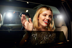 Glamorous woman waving through the window of a limousine Stock Image