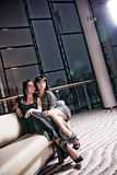 Glamorous Women. Two glamorous women sitting on a comfortable sofa in a luxurious house Royalty Free Stock Photography