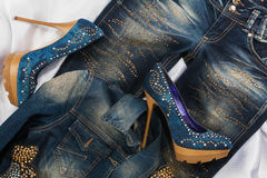 Glamorous women's fashion, shoes in rhinestones, lying on jeans and denim jacket Stock Photos