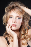 Glamorous young blonde woman over black Royalty Free Stock Image