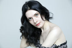 Glamorous young brunette woman with beautiful skin. Glamorous young brunette woman on grey background Royalty Free Stock Photo