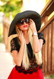 Glamorous young lady in big black hat in summer park Stock Image