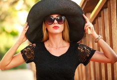 Glamorous young lady in big black hat in summer park Stock Photography
