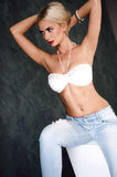 Glamorous young sexy blond woman wearing white bra and jeans with red lips Royalty Free Stock Images