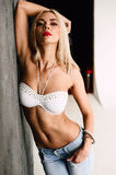 Glamorous young sexy blond woman wearing white bra and jeans with red lips Stock Photography