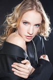 Glamorous young woman in a black jacket. Young beautiful blond woman in a black man's jacket over dark background Stock Image