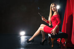 Glamorous young woman with cigarette sitting on Royalty Free Stock Photos