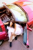 Glamorous Young Woman Getting Out of Red Sports Car Stock Photography