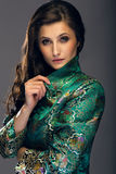 Glamorous young woman in green japanese style jacket looking str Stock Photography