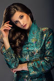 Glamorous young woman in green japanese style jacket looking str Stock Photos