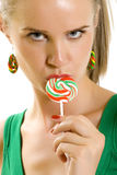Glamorous young woman licking lollypop. Over white background Stock Photo