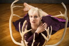 Glamorous young woman lying on hardwood floor with caribou antle. Beautiful young woman in purple dress lying on her stomach among caribou antlers on a hardwood Royalty Free Stock Photo