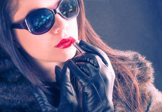 Glamorous young woman paint her lips, lights reflection on sunglasses Stock Images