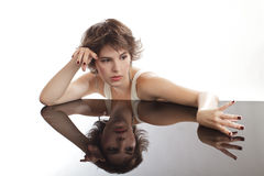 Glamorous young woman rests on mirrored surfac Royalty Free Stock Photos