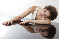 Glamorous young woman rests on mirrored surface Royalty Free Stock Images