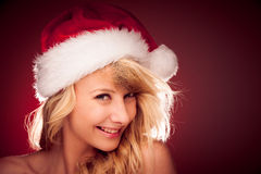 Glamorous young woman with Santa claus hat sending best  wishes Royalty Free Stock Photography
