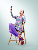 Glamorous young woman sitting on chair making selfie Royalty Free Stock Images