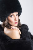 Glamorous young woman wearing black fur coat and hat Stock Image