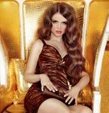 Glamorös kvinna med långt hårsammanträde i lyxig guld- armch Arkivbild