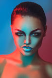 Glamour adult brunette with make up in red and blue lights Royalty Free Stock Image