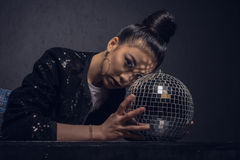 Glamour asian girl posing with disco ball and looking at camera isolated on grey Royalty Free Stock Photos