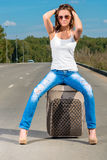 Glamour beautiful girl with a suitcase on the road Royalty Free Stock Images