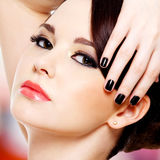 Glamour beautiful woman with black nails. Face of the beautiful young woman with black nails looking at camera royalty free stock photography