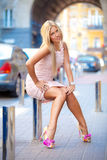 Glamour blond girl in pink dress posing on street Stock Photo