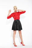 Glamour. Blonde Posing in Red Blouse and Black Skirt Royalty Free Stock Images