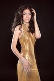 Glamour brunette girl in Fashion golden dress isolated on black Stock Photo