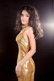 Glamour brunette girl in Fashion golden dress isolated on black Stock Images