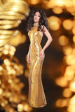 Glamour brunette girl in Fashion golden dress isolated on holiday lights background. Elegant lady with Long curly hair, beauty ma. Keup, luxury jewelry royalty free stock image