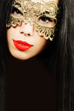 Glamour brunette woman in golden mask Royalty Free Stock Photo