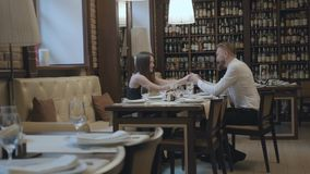 Glamour brunette woman and a handsome bearded blond man sitting at the table in front of each other. The man telling. Good words to his girlfriend then kisses stock video
