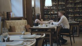 Glamour brunette woman and a handsome bearded blond man sitting at the table in front of each other. The man telling. Good words to his girlfriend then kisses stock video footage