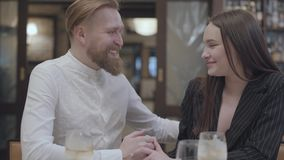 Glamour brunette woman and a handsome bearded blond man sitting at the table. The man telling good words to his. Glamour brunette woman and a handsome bearded stock footage