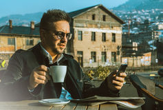 Glamour business man have some fun with cup of coffee and mobile. Phone outdoors Stock Photo