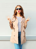 Glamour cool young woman with red lips wearing a black sunglasses coat over grey Royalty Free Stock Photography