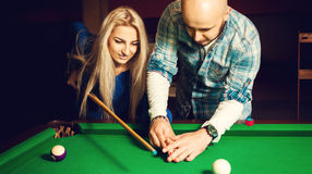 Glamour couple plays billiard for the first time Royalty Free Stock Photos