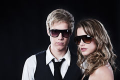 Glamour couple in sunglasses. Young handsome man and young pretty woman in sunglasses Stock Image